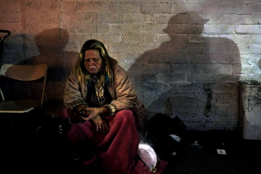 FILE - In this Thursday, March 21, 2013 file photo, a homeless woman has a bite to eat in the Skid Row area of Los Angeles. A new study finds a growing percentage of women living on Los Angeles' Skid Row are older, with the median age increasing from 44 to 50. Skid Row's total population is about 10,000, including more than 1,700 living in the streets, according to the Los Angeles Times. Officials estimate a quarter of the homeless are women. (AP Photo/Jae C. Hong, File)