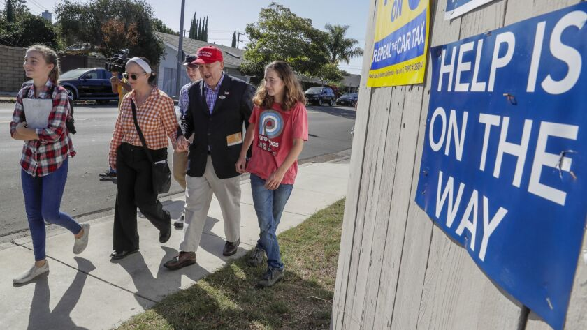 Republican Rep. Dana Rohrabacher walks with his wife, Rhonda, daughters Annika, left, and Tristen, and his son, Christian, back, as he drops off a mail-in ballot Tuesday at the Boys and Girls Club of Costa Mesa.