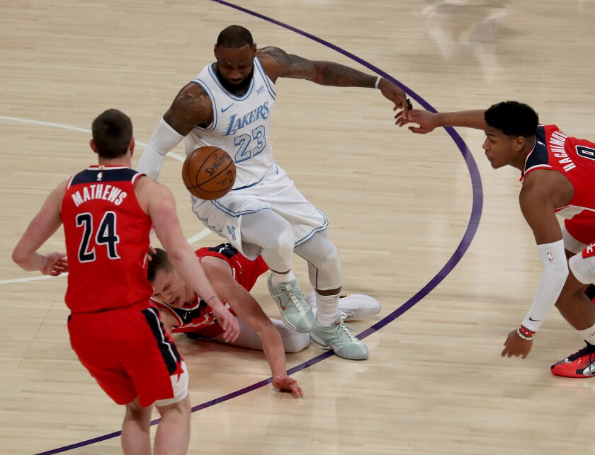 LeBron James fights for control of the ball against a trio of Washington Wizards players.