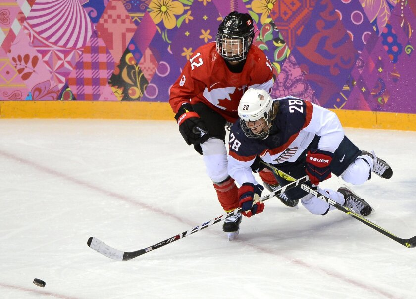 Canada's Meaghan Mikkelson knocks down USA's Amanda Kessel during the gold medal game at the Bolshoy Ice Dome during the Winter Olympics in Sochi, Russi.