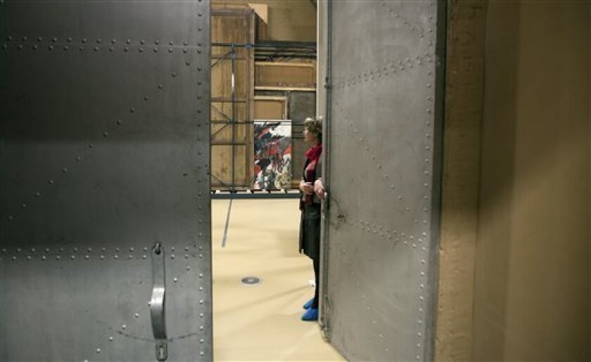 """Press and communications officer Veronique Van Passel opens giant steel doors which lead to an interior warehouse in the Antwerp Royal Museum of Fine Arts in Antwerp, Belgium on Thursday, April 4, 2013. Just as the famous Amsterdam Rijksmuseum in neighbouring Netherlands has returned """"The Night Watch"""" of its most famous painter, Rembrandt van Rijn, back in the main building after a ten-year renovation, Antwerp is hiding five oversized Rubens paintings in a special depot to protect them against t"""