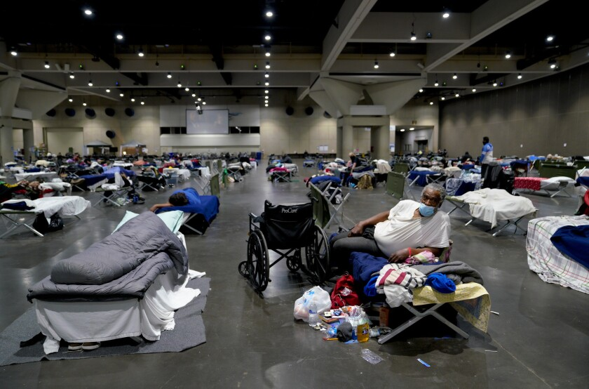 James Sneed, relaxing on his cot, has been staying at the homeless shelter inside the San Diego Convention Center.