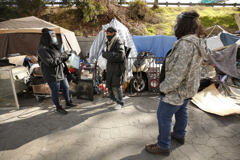 Three people at a homeless camp.