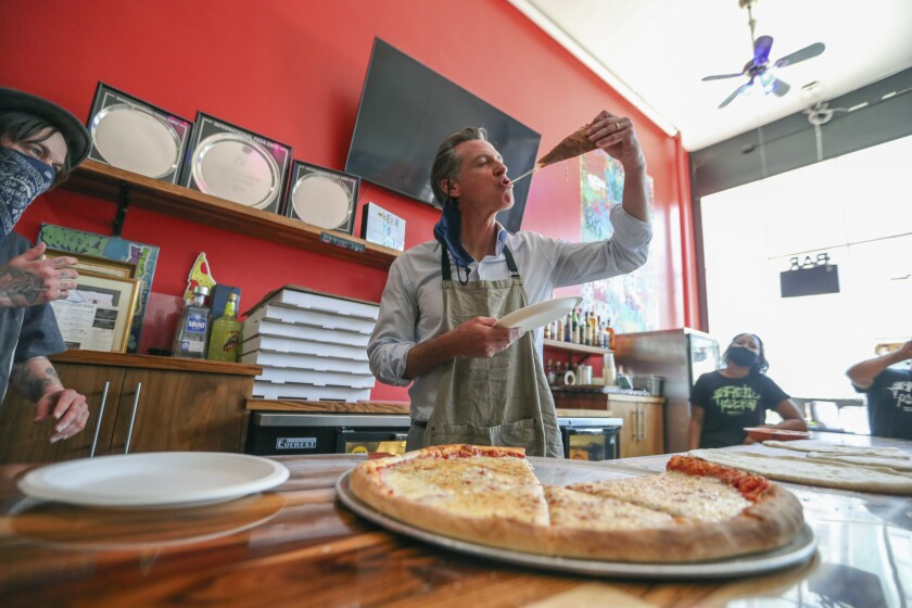 """Graffiti Pizza executive chef Matt Molina, left, looks on as California Gov. Gavin Newsom tries a slice of pizza during a visit in Oakland, Calif., on Thursday, June 17, 2021. A man has been arrested on suspicion of assaulting Newsom during his visit to downtown Oakland, authorities said Friday, June 18. Newsom was walking to a barbershop and pizzeria in Old Oakland to promote small businesses when he was """"approached by an aggressive individual,"""" said Fran Clader, director of communications for the California Highway Patrol, which provides security for the governor. (Ray Chavez/Bay Area News Group via AP)"""