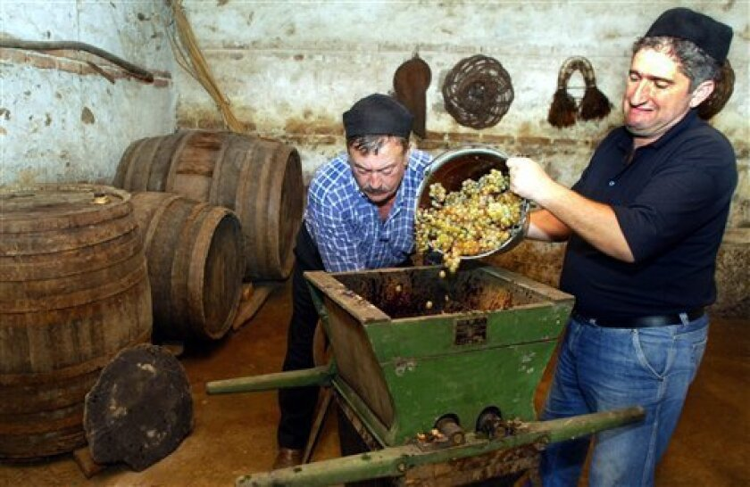 FILE - In this Sunday, Sept. 24, 2006 file photo, Nikoloz Mamiashvili and Amiran Getiashvili, left, press grapes in a local wine cellar in the wine rich Kakheti region of Georgia, about 100 km (62 miles) east of Tbilisi. Russia on Monday, Feb. 4, 2013, held talks on whether to resume Georgian wine imports after a seven-year ban, the first tentative step toward repairing the ruptured ties between the two ex-Soviet neighbors. Russia banned the imports of Georgian wine, mineral water, fruits and vegetables in 2006 amid rising political tensions in the run-up to a 2008 war. (AP Photo/ Shakh Aivazov, file)