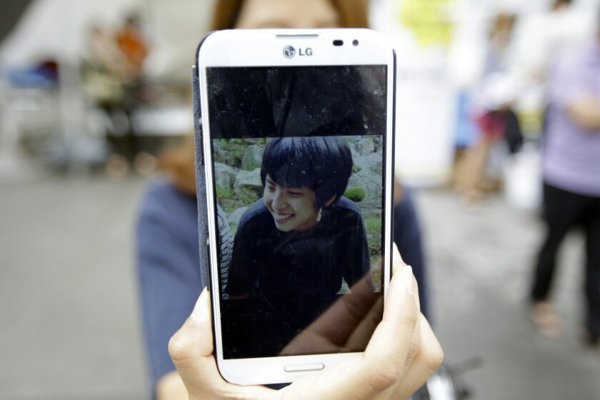 In this Wednesday, Aug. 13, 2014 photo, a picture of Park Seong-ho, a 17-year-old student killed in the ferry Sewol sinking, is shown by his sister Park Bona's smartphone in Seoul, South Korea. The relatives of some of the more than 300 people killed in the April ferry sinking are hoping Pope Francis' visit to South Korea will provide both solace for their anger and grief - and a boost in their struggle against the government. Park Youn-oh, the father of Seong-ho, said he was overwhelmed when he saw the pope's plane Thursday, Aug. 14, 2014 and briefly met the pontiff. (AP Photo/Lee Jin-man)