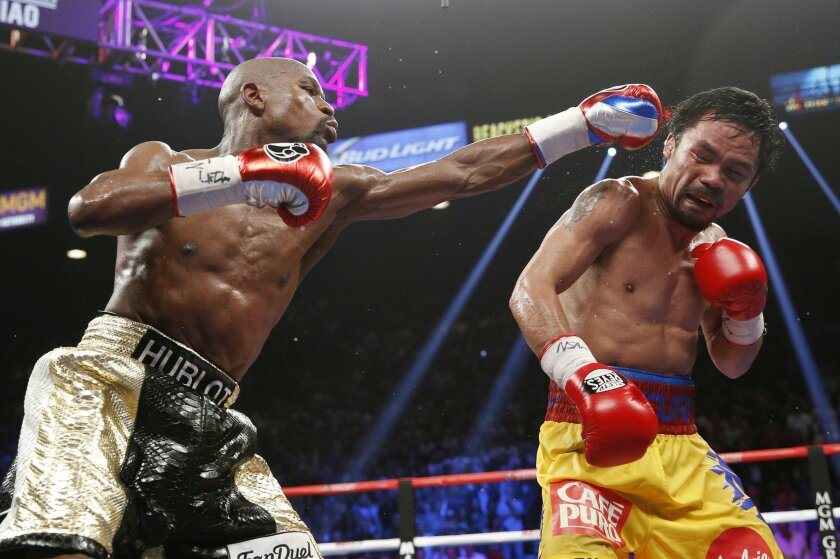 FILE - In this May 2, 2015 file photo, Floyd Mayweather Jr., left, hits Manny Pacquiao, from the Philippines, during their welterweight title fight in Las Vegas. The broadcast of fight was marred by technical snafus and got sucker punched by Internet streamers, exposing the industry's vulnerabiliti