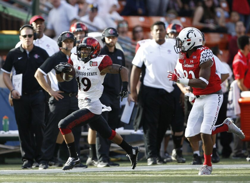 Dec 24, 2015; Honolulu, HI, USA; San Diego State Aztecs running back Donnel Pumphrey (19) makes a run down the sideline while being chased by Cincinnati Bearcats corner back Linden Stephens (32) during the second quarter in the 2015 Hawaii Bowl at Aloha Stadium.