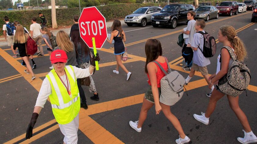 Crosswalk attendant Roberta Ray stops traffic along Eastbluff Drive as students make their way to Corona del Mar High School in 2013.