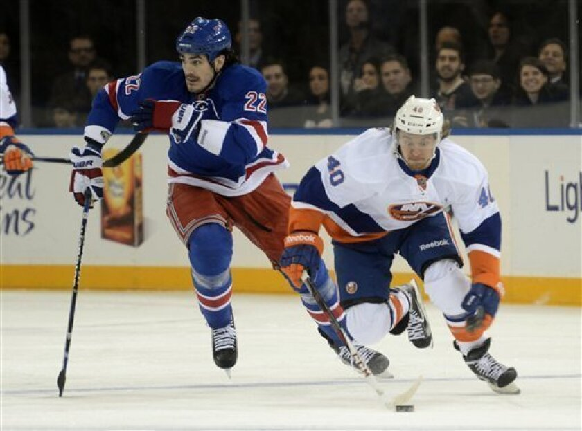 New York Islanders' Michael Grabner, right, and New York Rangers' Brian Boyle chase the puck during the first period of an NHL hockey game at Madison Square Garden in New York, Thursday, Feb. 14, 2013. (AP Photo/Henny Ray Abrams)