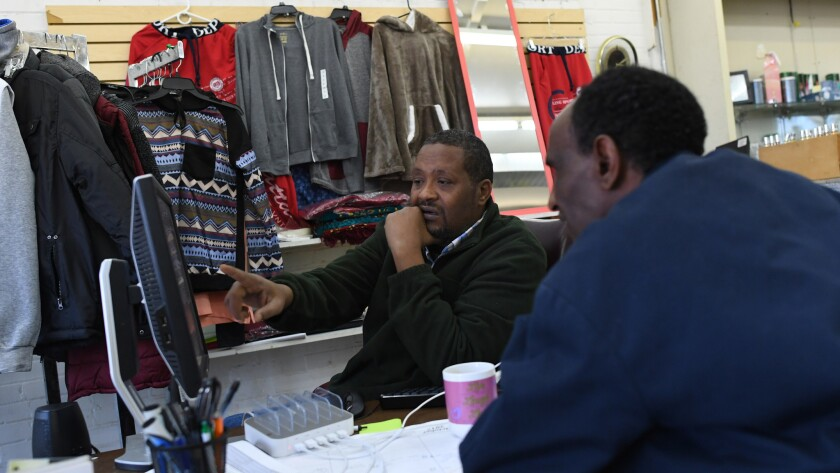 Somali immigrant Khadar Ducaale, left, helps Ahmed Omar look for a job in Fort Morgan, Colo. Ducaale runs a small business that caters to new immigrant arrivals.