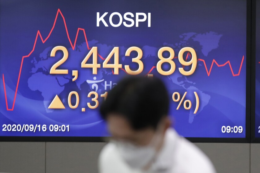 A currency trader stands near a screen showing the Korea Composite Stock Price Index (KOSPI) at the foreign exchange dealing room in Seoul, South Korea, Wednesday, Sept. 16, 2020. Shares were mostly higher in Asia on Wednesday after advances for big technology companies carried Wall Street to further gains overnight. (AP Photo/Lee Jin-man)
