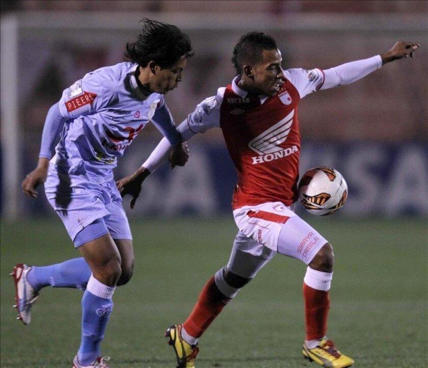 Wilder Medina (d) de Santa Fe disputa el balón con Rolando Bogado (i) de Real Garcilaso durante el partido por los cuartos de final de la Copa Libertadores, en Cuzco (Perú). EFE
