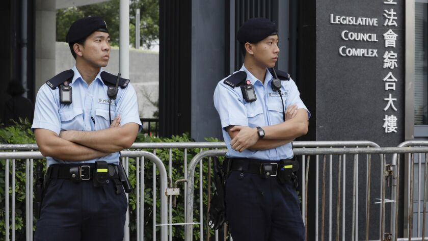 Police stand guard at fencing surrounding the Legislative Council to help block protesters during up