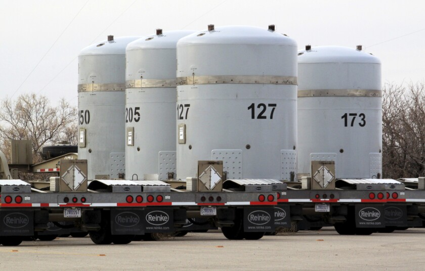 FILE - In this March 6, 2014, file photo, empty nuclear waste shipping containers sit in front of the Waste Isolation Pilot Plant near Carlsbad, N.M. The U.S. government's efforts to clean up decades worth of Cold War-era waste from nuclear research and bomb making at federal sites around the country has chugged along, often at a pace that watchdogs and other critics say threatens public health and the environment. Now, fallout from the global coronavirus pandemic is resulting in more challenges as the Waste Isolation Pilot Plant, the nation's only underground repository for nuclear waste, finished ramping down operations Wednesday, April 1, 2020, to keep workers safe. (AP Photo/Susan Montoya Bryan, File)