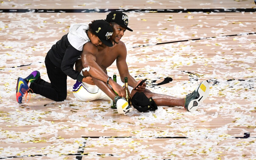 Guard Rajon Rondo and his son, Rajon Jr., celebrate on the court after the Lakers won the title on Sunday.