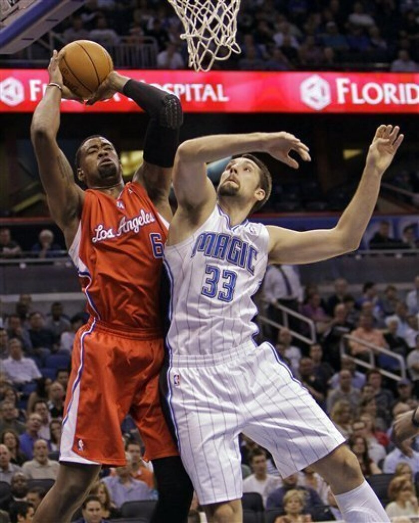 Los Angeles Clippers' DeAndre Jordan (6) takes a shot as Orlando Magic's Ryan Anderson (33) defends during the first half of an NBA basketball game Monday, Feb. 6, 2012, in Orlando, Fla. (AP Photo/John Raoux)