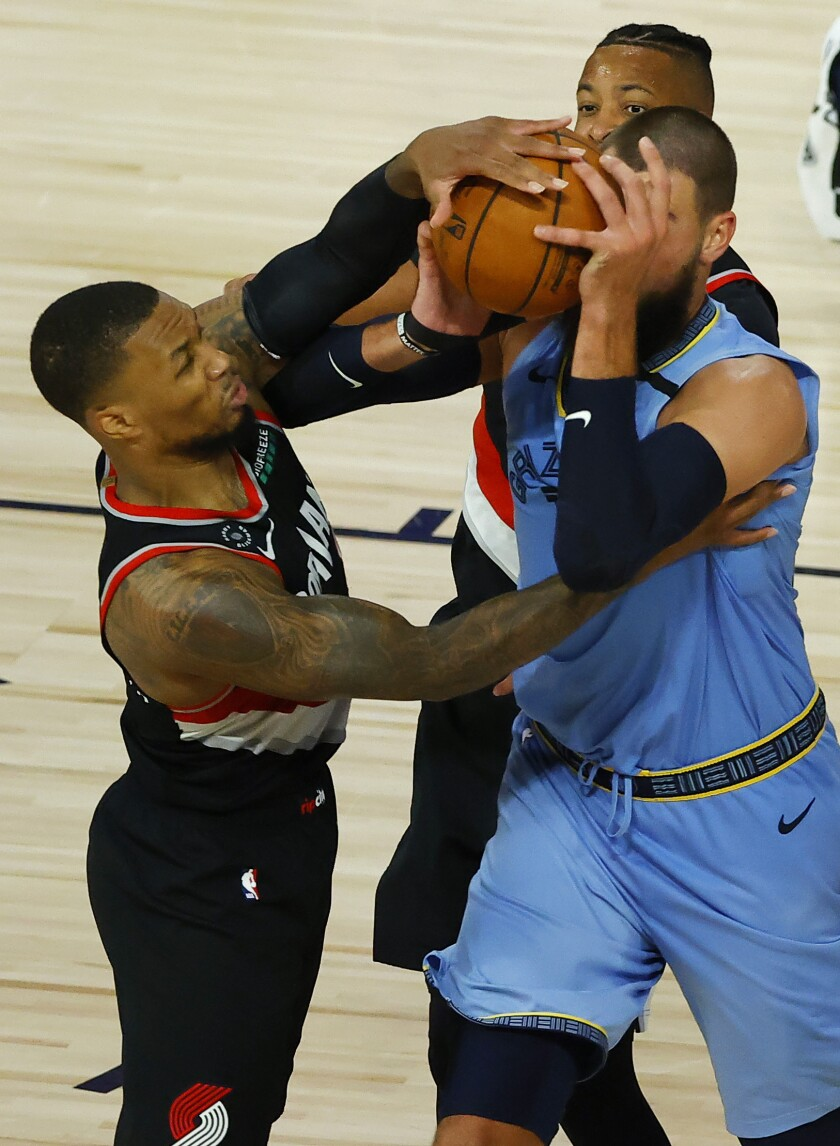 Portland Trail Blazers' Damian Lillard, left,and Memphis Grizzlies' Jonas Valanciunas tangle during the second half of an NBA basketball game Saturday, Aug. 15, 2020, in Lake Buena Vista, Fla. (Kevin C. Cox/Pool Photo via AP)