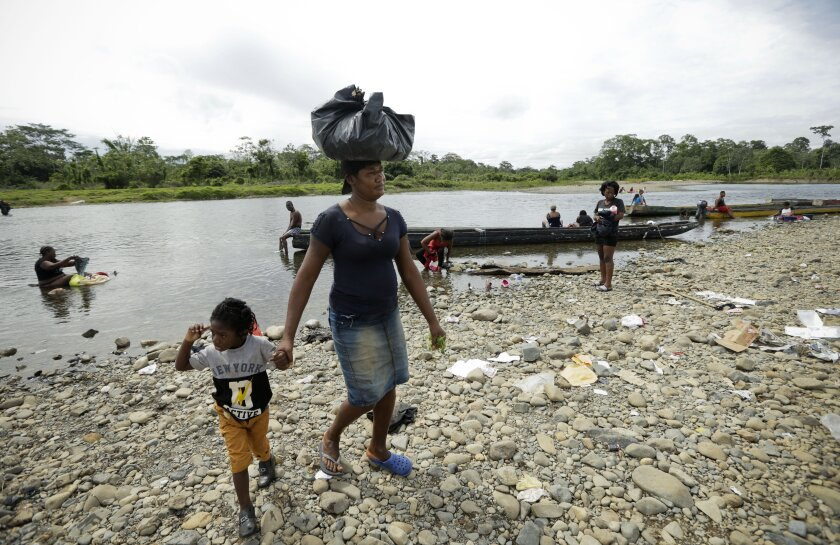 FILE - In this May 25, 2019 file photo, a Haitian woman reaches the shore after wading across the Tuquesa river, holding her child, in Bajo Chiquito, Darien province, Panama. The government of Panama said Monday, August 3, 2020, that it is proposing humanitarian flights home for Haitian migrants confined in camps on the country's southern border. (AP Photo/Arnulfo Franco, File)