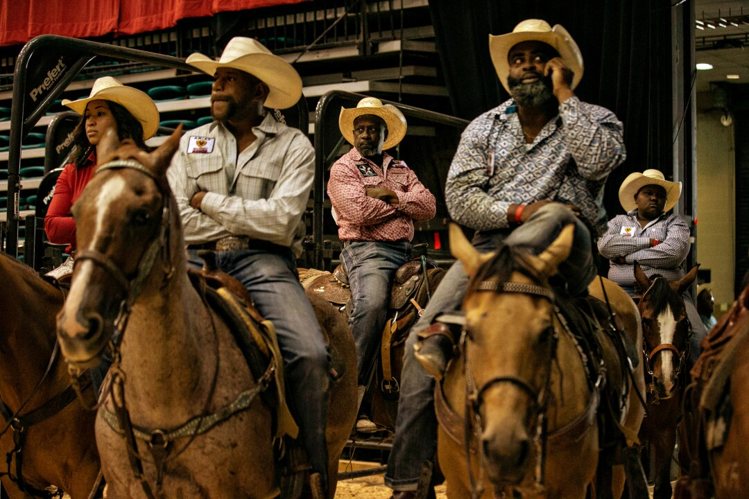 Contestants relax on their horses waiting for the final of the Bill Pickett Invitational Rodeo.