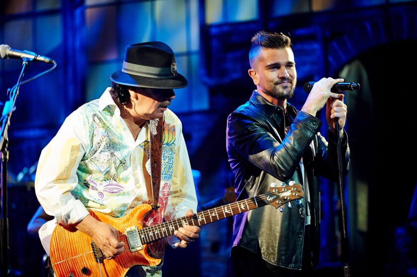 Carlos Santana, left, and Juanes perform during the Univision upfront presentation in New York.