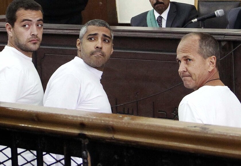 FILE - In this March 31, 2014 file photo, Al-Jazeera English producer Baher Mohamed, left, Canadian-Egyptian acting Cairo bureau chief Mohammed Fahmy, center, and correspondent Peter Greste, right, appear in court along with several other defendants during their trial on terror charges, in Cairo. An Egyptian court on Saturday, Aug. 29, 2015, sentenced the three Al-Jazeera English journalists to three years in prison. (AP Photo/Heba Elkholy, El Shorouk, File) EGYPT OUT