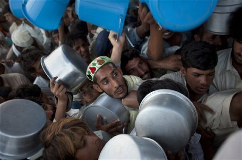 Displaced men and boys struggle to get their daily ration during a food distribution at the Chota Lahore refugee camp, at Swabi, in northwest Pakistan, Saturday, May 30, 2009. The Taliban have fled the Pakistani army's advance on the main town in the Swat Valley, delivering the military a strategic
