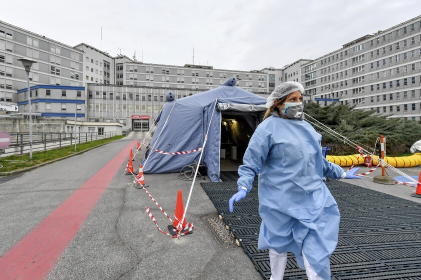 A paramedic walks out of a tent that was set up in front of the emergency ward of the Cremona hospital in northern Italy on Feb. 20.