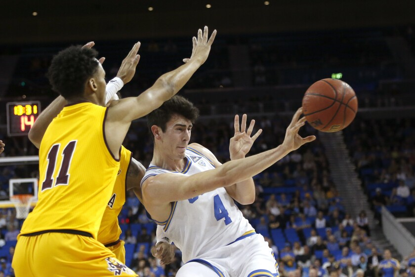 UCLA guard Jaime Jaquez Jr. (4) passes the ball while defended by Arizona State players during the first half on Thursday at Pauley Pavilion.