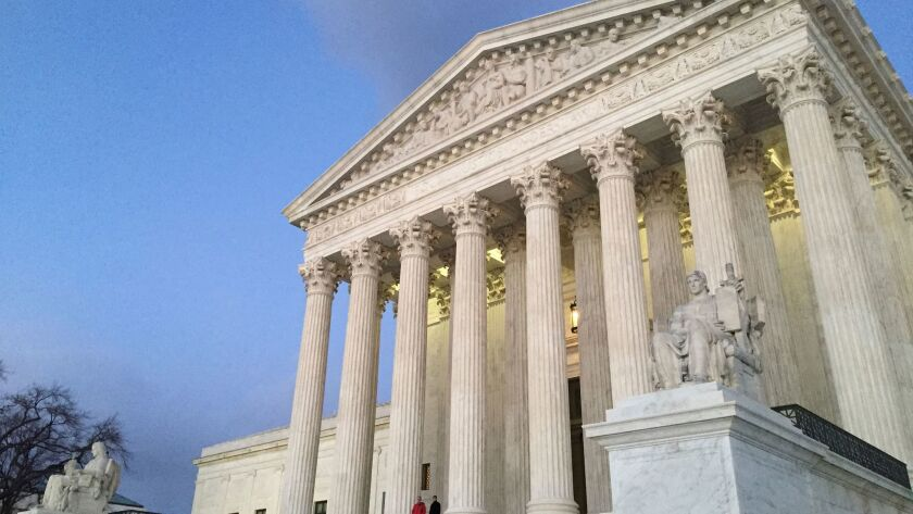 FILE - In this Feb. 13, 2016, file photo, people stand on the steps of the Supreme Court at sunset i