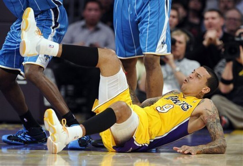 Los Angeles Lakers forward Matt Barnes lands on the floor after getting tied up with New Orleans Hornets guard Jarrett Jack as they went after a rebound during the first half of their NBA basketball game, Friday, Jan. 7, 2011, in Los Angeles. Barnes injured his knee on the play when he landed. (AP Photo/Mark J. Terrill)