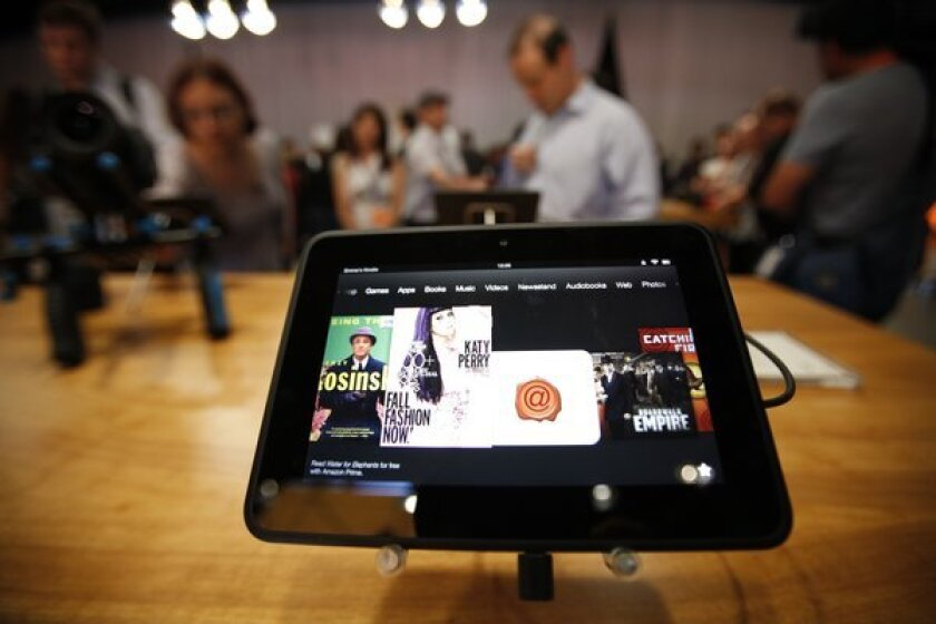 Journalists try out the Amazon Kindle Fire HD in Santa Monica last year. The version that costs $399 comes with the ability to connect to AT&T's 4G LTE network for data services.