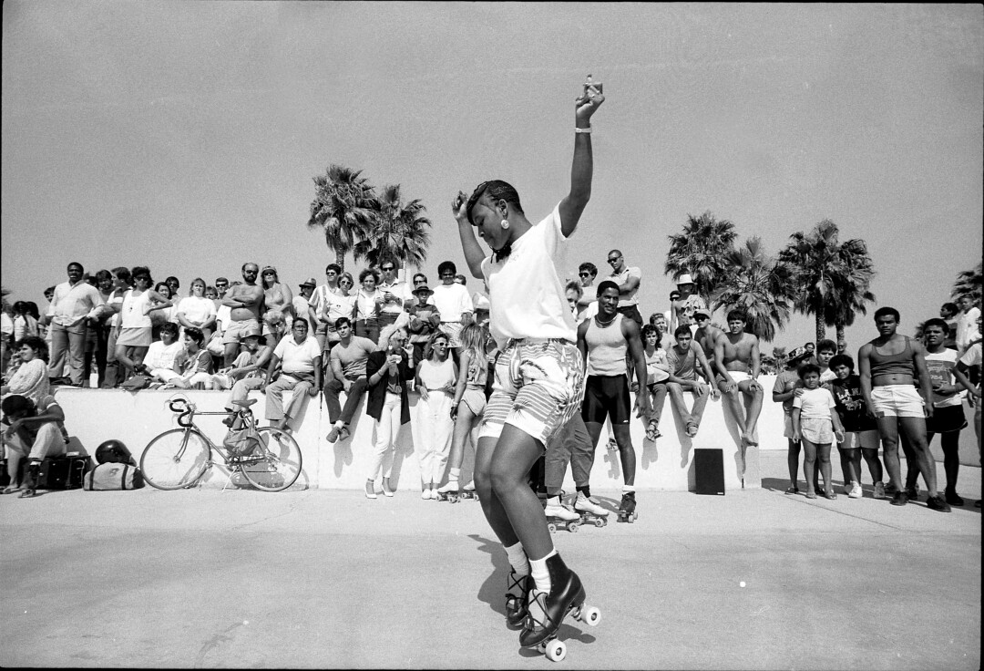 A roller skater performs for a crowd at Venice Beach in 1986.