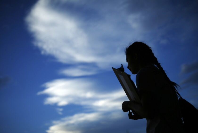 A young woman waits clipboard in hand to register people to vote in Las Vegas in this 2016 file photo.