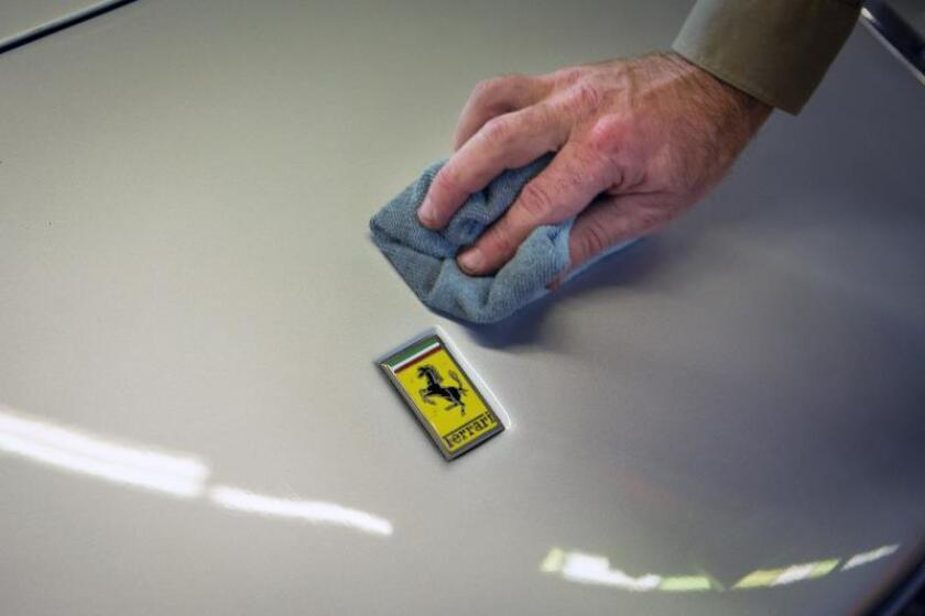 Un expositor limpia la carrocería de un vehículo Ferrari. EFE/Archivo