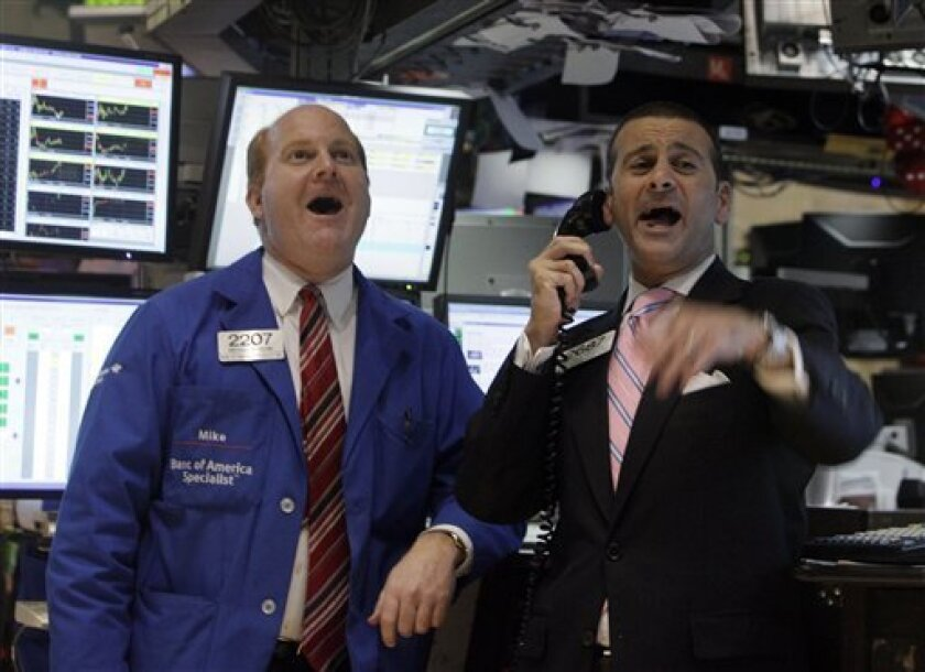 Specialists Michael Scavone, left, and Michael Sollitto reacted yesterday on the floor of the New York Stock Exchange as the Dow Jones Industrial Average crossed the 10,000 mark. (AP Photo/Richard Drew)