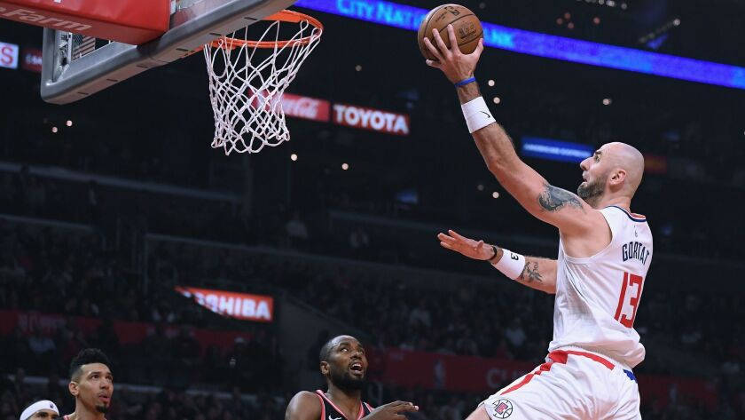 Marcin Gortat of the Clippers drives to the basket near Serge Ibaka of the Toronto Raptors during Tuesday's game at Staples Center.