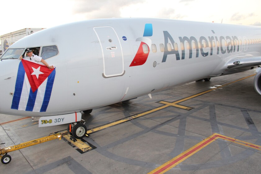Kevin Mase, an American Airlines chief pilot, drapes a Cuban flag from an AA Boeing 737 in December, after the United States and Cuba announced an agreement to restore commercial air service between the two countries.