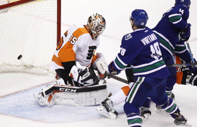 Vancouver Canucks Jake Virtanen (18) scores against Philadelphia Flyers goaltender Steve Mason during third period NHL hockey action in Vancouver, British Columbia, on Monday, Nov. 2, 2015. (Ben Nelms/The Canadian Press via AP)