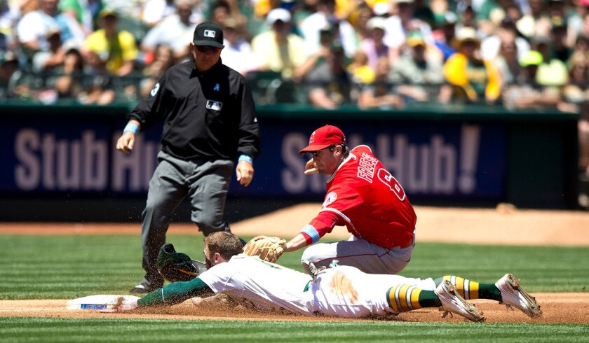 Oakland Athletics' Brett Lawrie is tagged out attempting to steal third base by Los Angeles Angels of Anaheim's David Freese in front of umpire Greg Gibson during the second inning on Sunday. A's beat the Angels, 3-2.