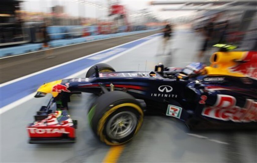 Red Bull Formula One driver Mark Webber of Australia drives out of his pit lane garage during the third practice session for the Singapore Formula One Grand Prix on the Marina Bay City Circuit in Singapore, Saturday, Sept. 22, 2012. (AP Photo/Mark Baker)