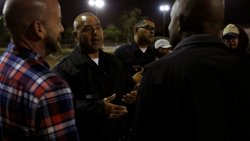 LAPD officers Oscar Casini, center left, and Roger Medina, center right, talk with Boyle Heights area residents during a  Summer Night Lights program at the Costello Recreation Center in Boyle Heights.