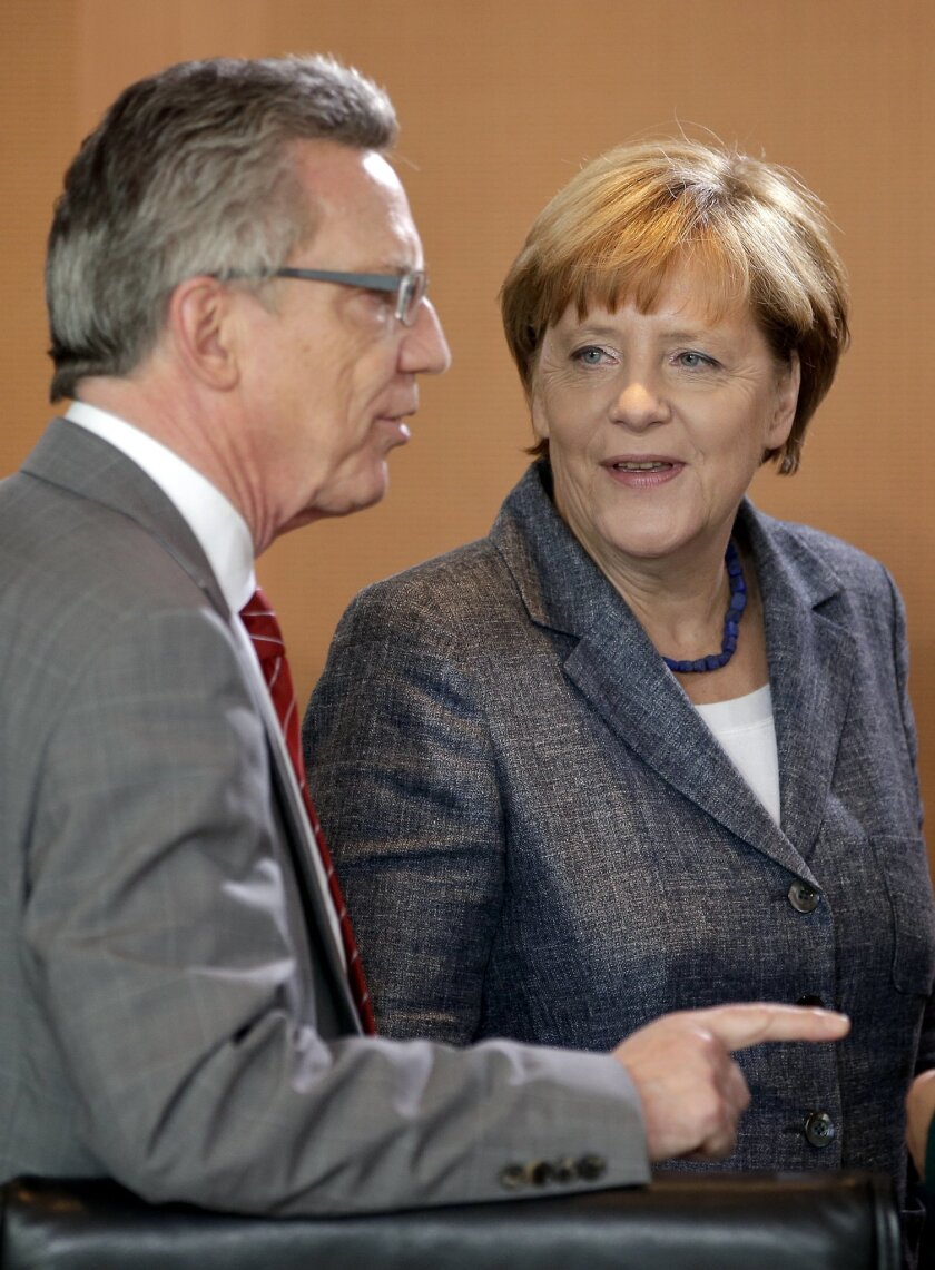German Chancellor Angela Merkel, right, talks to German Interior Minister Thomas de Maiziere, left, at the beginning of a special meeting of the cabinet on migrants at the chancellery in Berlin, Germany, Tuesday, Sept. 15, 2015. (AP Photo/Michael Sohn)