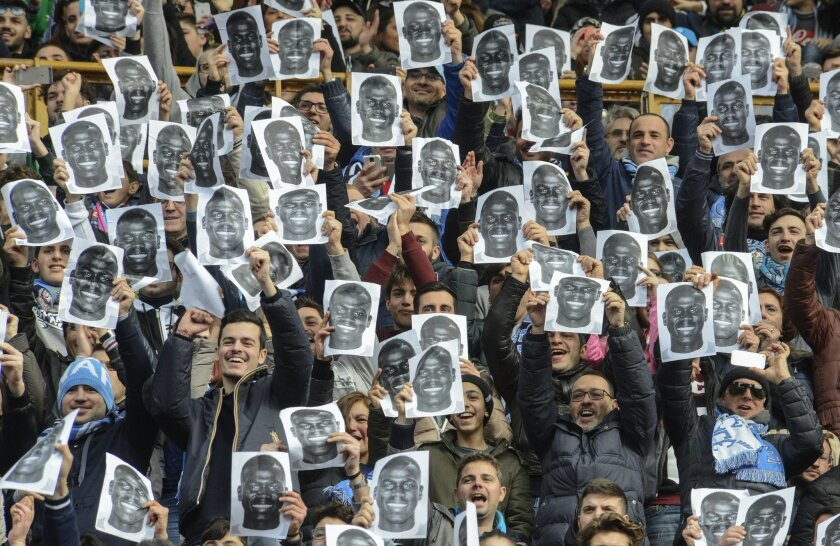Napoli supporters hold up prints of Napoli defender Kalidou Koulibaly's portrait in support of him, ahead of a Serie A soccer match between Napoli and Carpi, at the San Paolo stadium in Naples, Italy, Sunday, Feb. 7, 2016. Last week during the team's game against Lazio the match was suspended for f