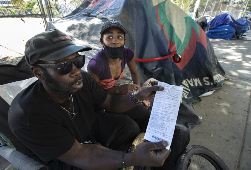 Alex Jones and his girlfriend, Maya Johnson, are shown at a homeless encampment near 1st and Spring streets in downtown L.A.