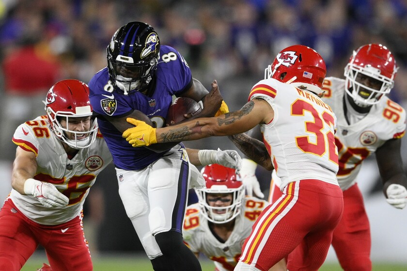 El quarterback de los Ravens Lamar Jackson (8) corre entre cuatro defensores de los Chiefs