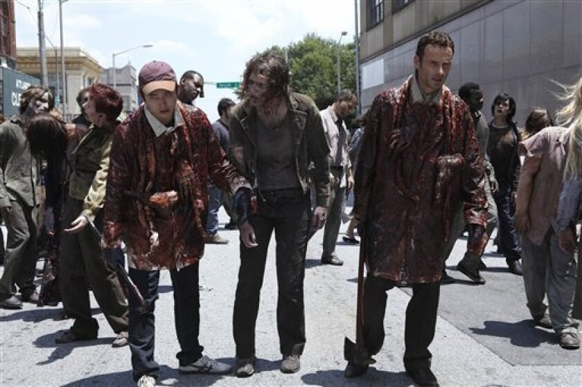 """In this publicity image released by AMC, Steven Yeun, left, and Andrew Lincoln, right, try to blend in with the zombie population in a scene from """"The Walking Dead."""" (AP Photo/AMC)"""