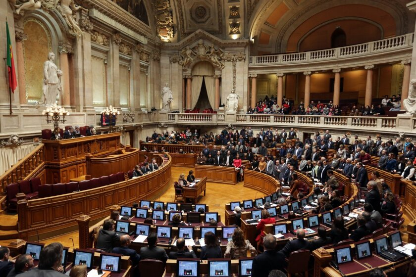 Members of parliament stand up, background right, to vote in favor of a bill that grants adoption rights to same-sex couples at the parliament in Lisbon, Wednesday, Feb. 10, 2016. Left-of-center parties in Portugal's Parliament have used their majority to overturn a presidential veto on bills that