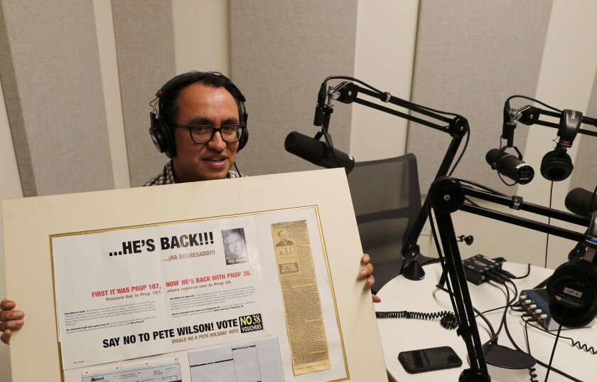 Gustavo Arellano holds a poster board with a campaign flier mounted next to a newspaper clipping.