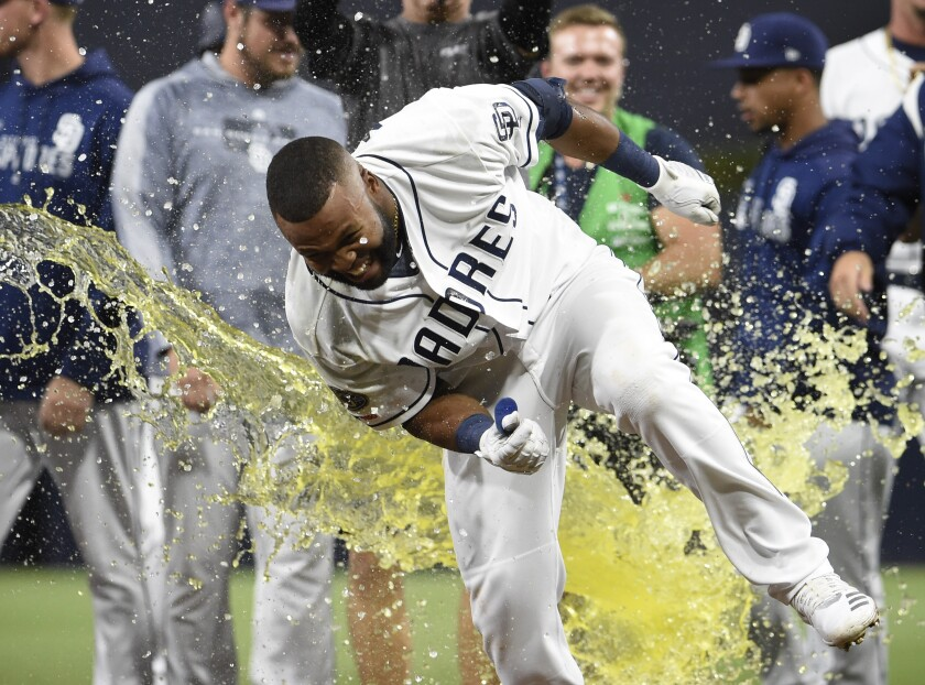 Manuel Margot tries to dodge a Gatorade shower during the celebration following his walk-off walk in Tuesday's 9-8 victory over Chicago Cubs in 10 innings at Petco Park.